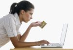 Teenage girl holding a credit card working on a laptop